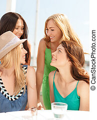 group of smiling girls in cafe on the beach - summer...