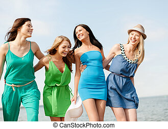 smiling girls walking on the beach - summer holidays and...