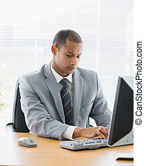 Concentrated businessman using computer at office