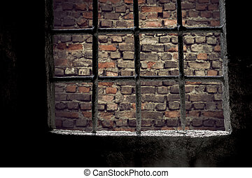 Brick wall viewed through prison window with metal bars