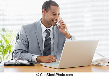 Businessman using laptop and phone at office desk -...