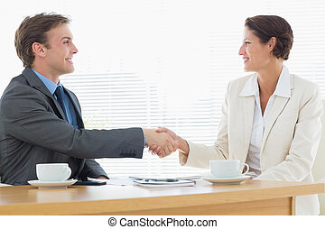 Smartly dressed couple shaking hands in business meeting -...