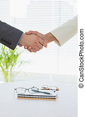Close-up of shaking hands over eye glasses and diary after a...