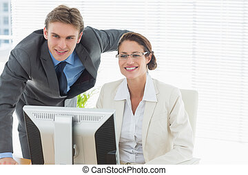 Confident smiling business couple with computer