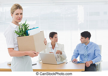 Businesswoman carrying her belongings with colleagues in background