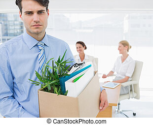 Businessman carrying his belongings with colleagues in background