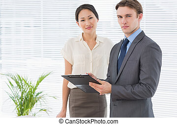Business colleagues with clipboard at office