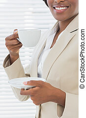Mid section of smiling businesswoman with a cup of tea -...