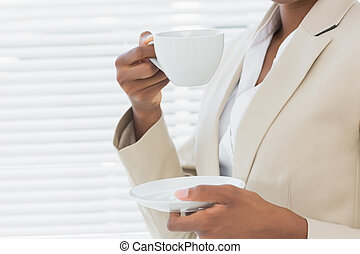 Mid section of elegant businesswoman with tea cup in office...
