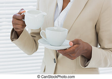Mid section of elegant businesswoman with tea cup - Close-up...