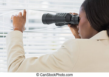 Businesswoman peeking with binoculars through blinds - Side...
