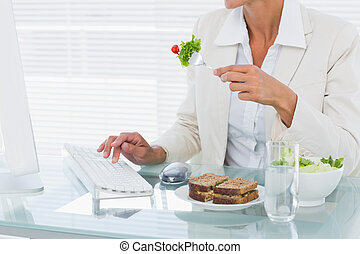 Businesswoman using computer while eating salad at desk -...