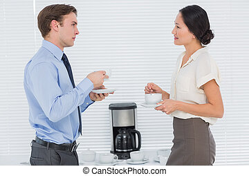 Business couple with tea cups chatting - Side view of young...