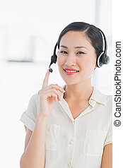 Beautiful smiling female executive with headset - Portrait...