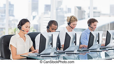 Colleagues with headsets using computers at desk - Group of...