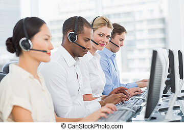 Business colleagues with headsets using computers at desk -...