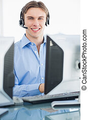 Male executive with headset using computer at desk -...