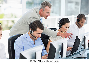 Manager looking at executives with headsets using computers...