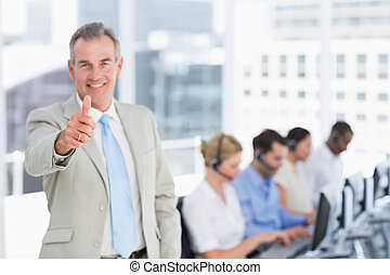 Businessman gesturing thumbs up with executives using...
