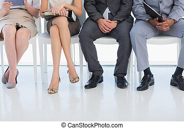 Low section of people waiting for job interview in office -...