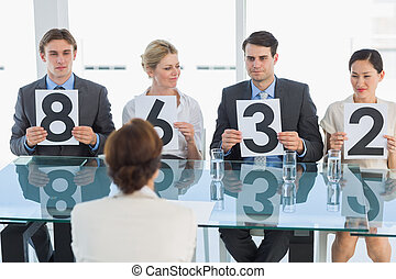 Judges in a row holding score signs - Group of panel judges...