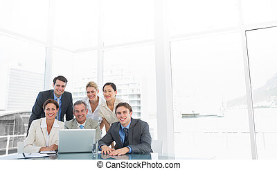 Business colleagues with laptop at office desk - Group of...
