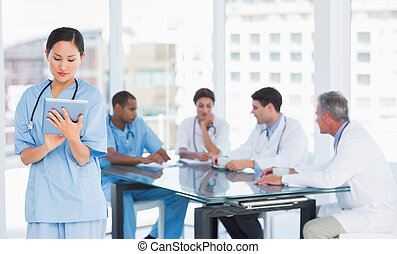 Female surgeon using digital tablet with group around table...