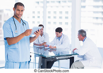 Male surgeon using digital tablet with group around table in background at hospital