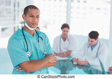 Surgeon standing with group around - Serious male surgeon...