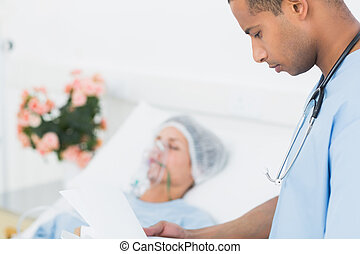 Doctor visiting patient in hospital - Side view of a doctor...