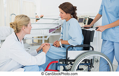 Doctor talking to a patient in wheelchair at hospital - Side...