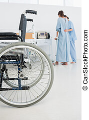 Doctor helping patient to walk with wheelchair in foreground...