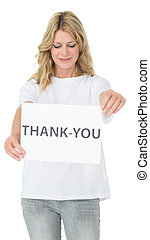 Smiling female volunteer holding 'thank you' paper - Smiling...