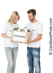 Smiling young couple carrying donation box over white...