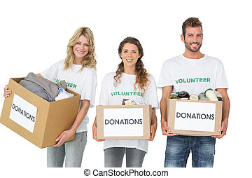 Portrait of three smiling young people with donation boxes...