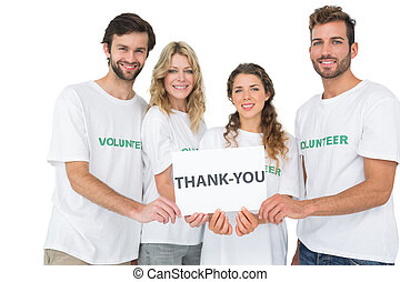 Portrait of happy volunteers holding 'thank you' board -...