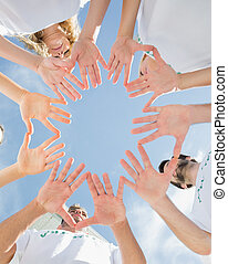 Volunteers with hands together against blue sky - Low angle...