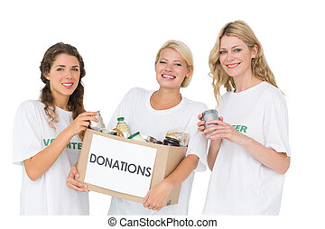 Portrait of three smiling young women with donation box over...