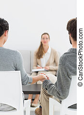 Blurred female financial adviser in meeting with couple -...