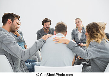 Group therapy in session sitting in a circle with therapist