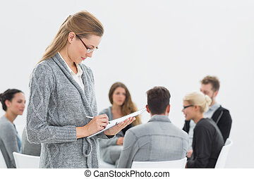 Therapist writing notes with group therapy in session -...