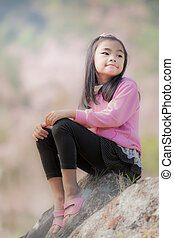 little asian girl sit on the rock with pink sakura and...