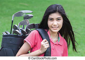 Young woman on a golf course on a sunny autumn day in the...