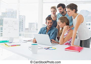 Casual business people using laptop together - Young casual...