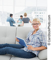 Woman using digital tablet with col - Portrait of a smiling...