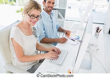 Casual young couple working on computers - Side view of...
