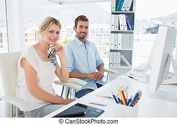 Portrait of smiling casual young couple with computer