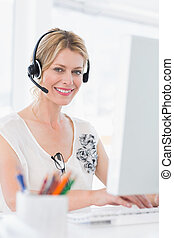 Portrait of a casual woman with headset using computer