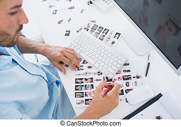 Male photo editor at work in the office - High angle view of...