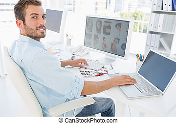 Male photo editor working on computer - Side view portrait...